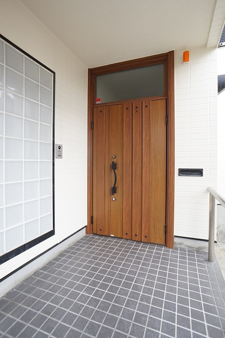 採光は上部から取り入れて玄関ドアは素材感際立つ木目柄に