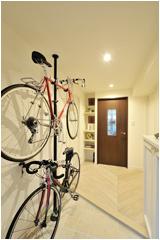 趣味の自転車がかっこよく並ぶ玄関は、洋室との壁を約45cm動かしてスペースを拡張。