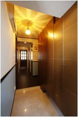 アンティーク照明の光が幻想的な玄関。壁はクロスにペイントして塗り壁風に。