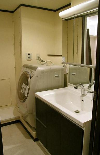 洗面台は大きく収納たっぷりのものを選び、ダークブラウンでシックな洗面室に
