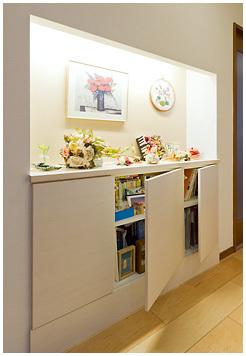 玄関入ってすぐの壁面に窪みを付けてニッチを設置。下が収納、上が照明付きの飾りスペース。