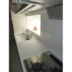 収納たっぷりのキッチンと個性的な壁紙選び