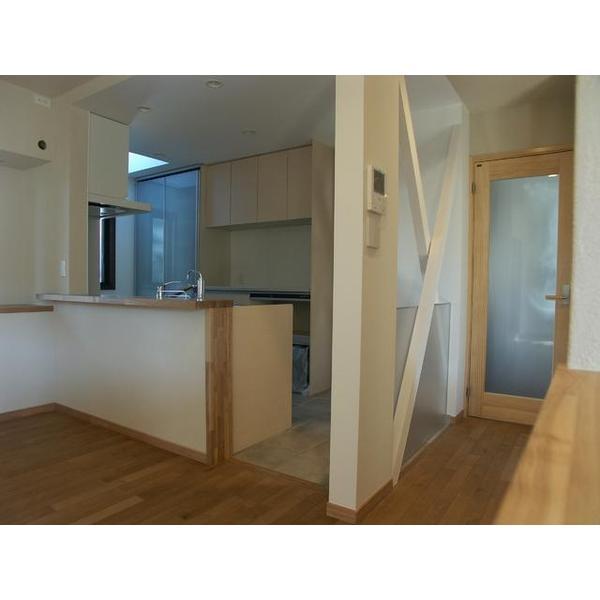 間取り変更による対面式キッチンの設置。床はタイル張り。撤去できない筋交い部分にアクリル板を設置。