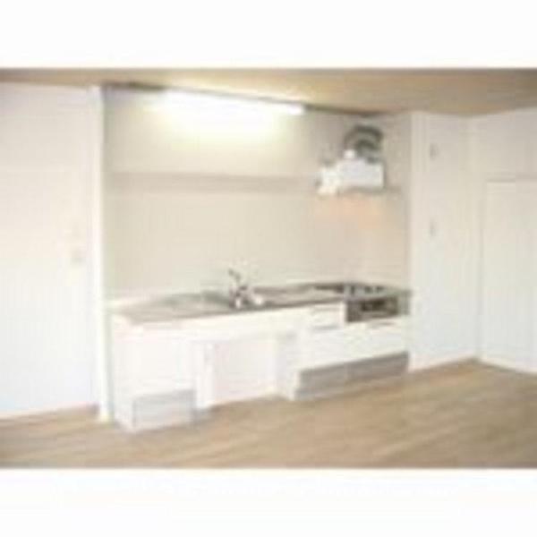 白を基調としたキッチンで、床は無垢のナラ材でフローリング。身長にあわせ天板まで800�oにしています。