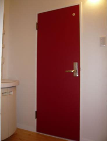 淡白になりがちな洗面室の扉を赤に