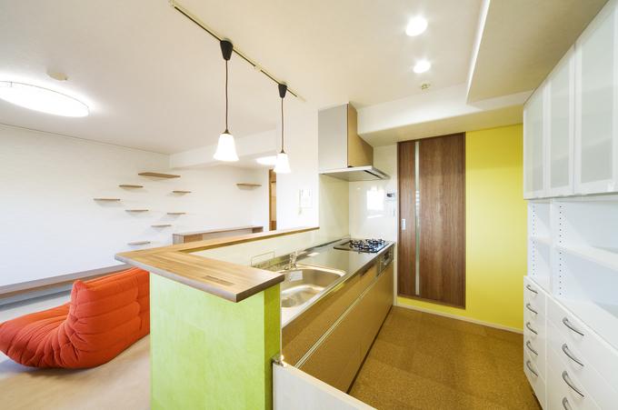 イエローの壁がおしゃれなリビングが見渡せる明るいキッチン