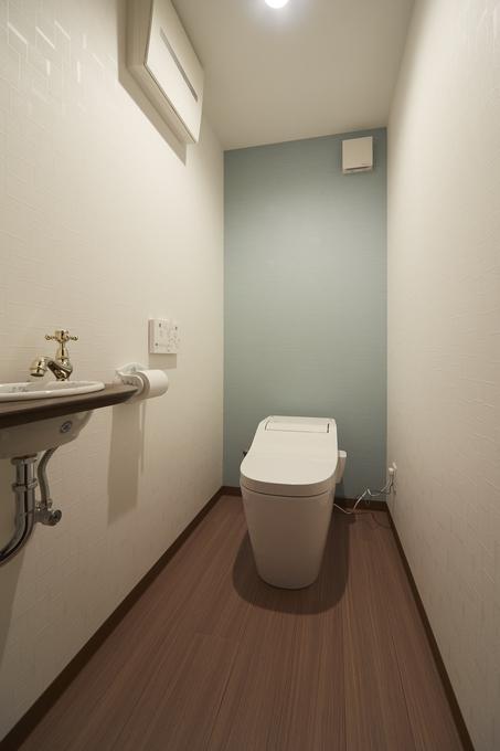 水色のアクセントクロスが映えるシンプルなトイレ